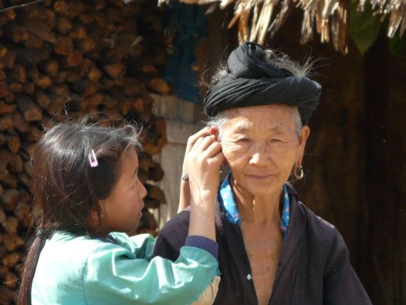 A young girl carefully cleaning the ear lobe of her grandma outside their home in the Laos